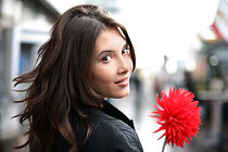 Beautiful woman with red flower walking