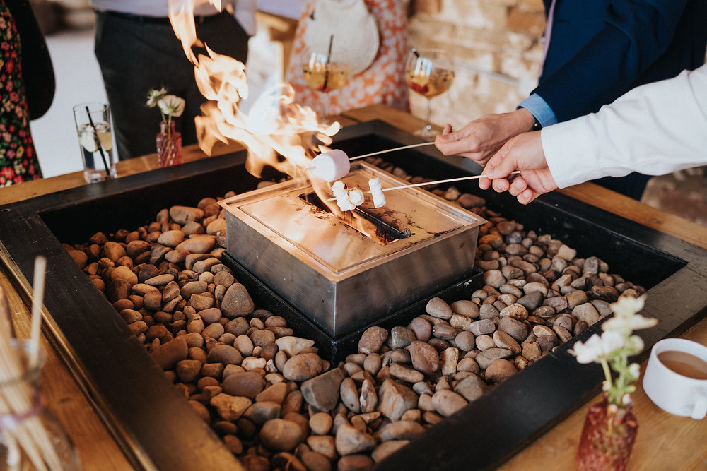 Toasting marshmallows on a firepit at a wedding