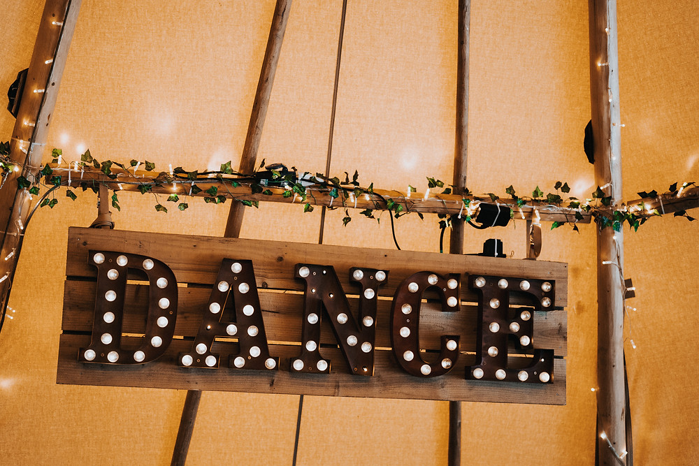 Carnival dance bulb sign in tipi for a wedding