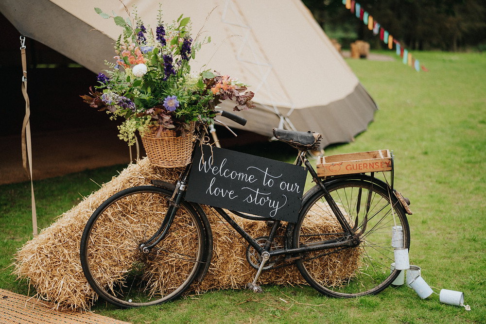 Vintage bike with flowers for a wedding, along with calligraphy chalkboard sign