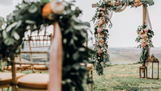 Image of a wooden ceremony arch festooned with white, pink and peach flowers