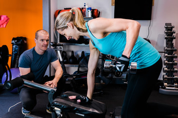 Personal trainer observing weight lfting technique