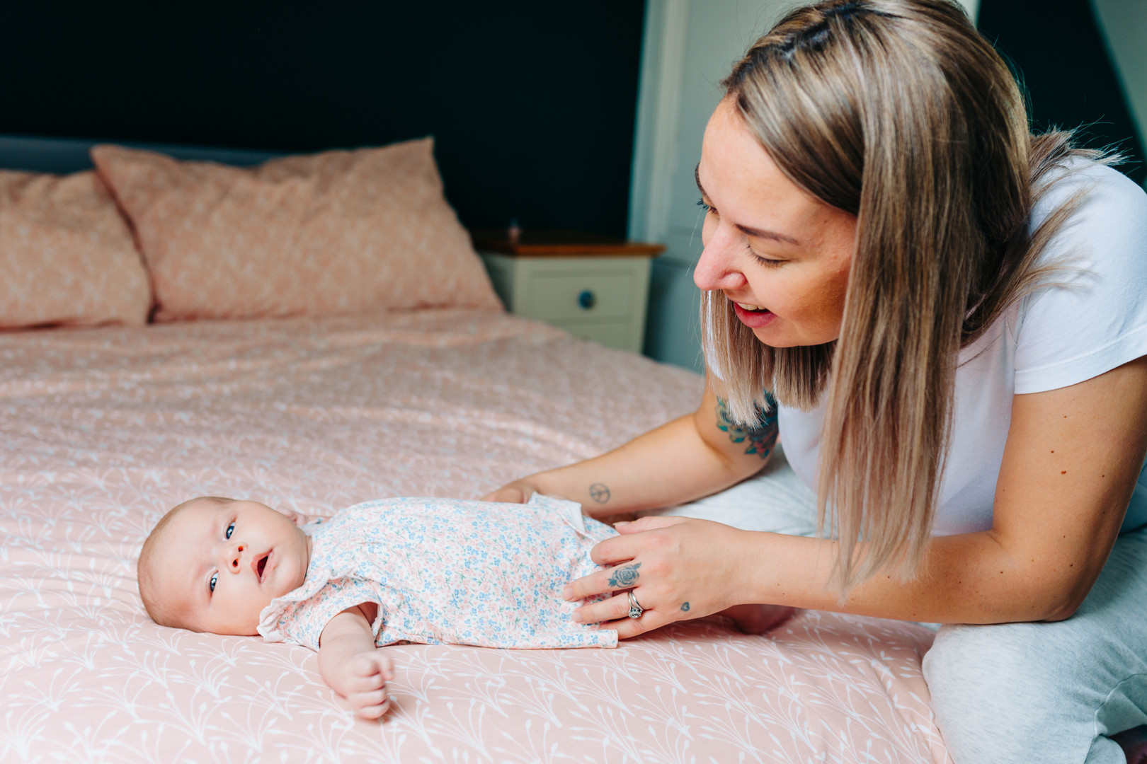 Baby on bed with mum looking lovingly. Newborn lifestyle photoshoot pose ideas.