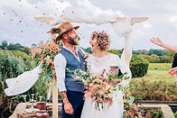 Outdoor Wedding photo of Bride and Groom under a wooden arch laughing as confetti swirls
