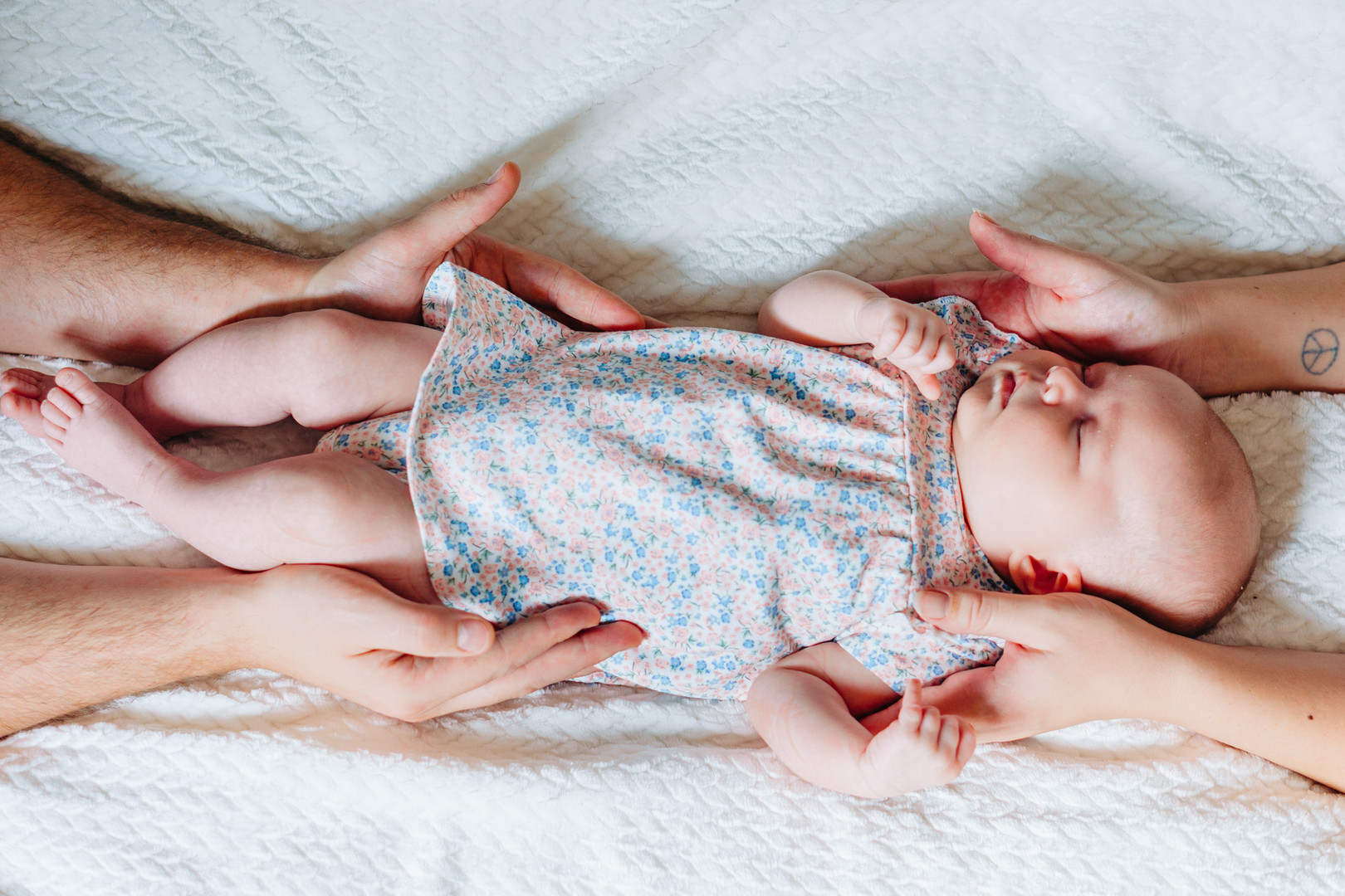 Sleeping baby cradled by mum and dad's hands. Newborn lifestyle photoshoot pose ideas.