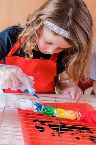 event photo of young girl adding dye to a colourful rainbow tie dye tshirt