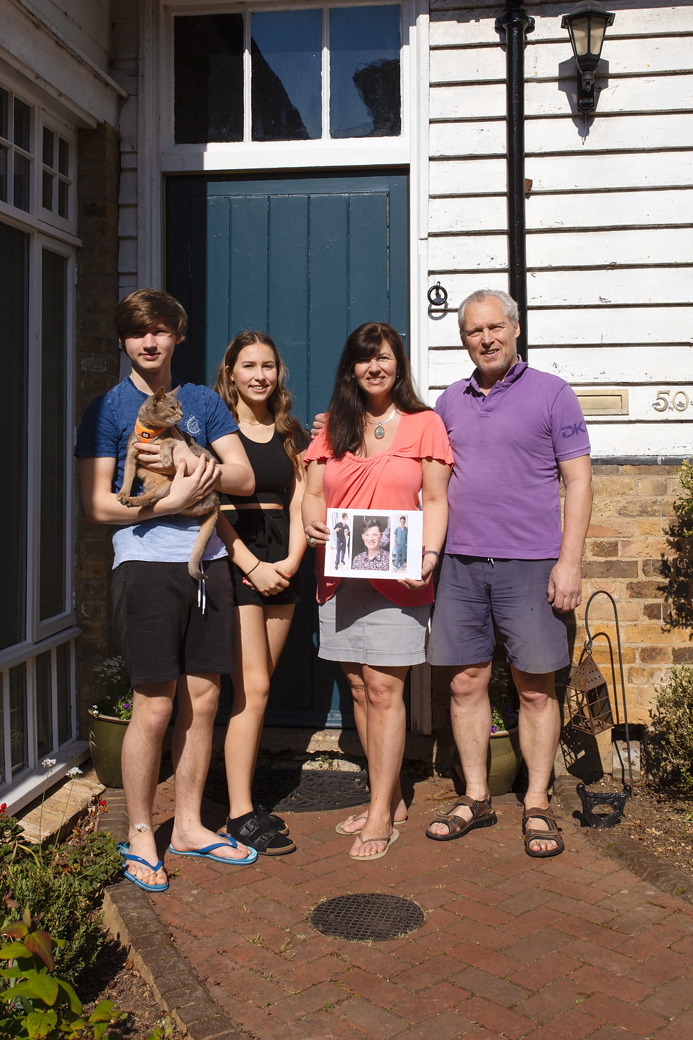 Family holding a photo of son absent due to his work as a doctor during the covid pandemic 2020