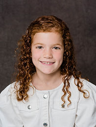 Studio headshot of girl with curly red hair on brown background