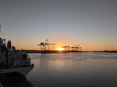 The sun sets over the ocean in Honolulu. Cranes and container ships are silhouetted against the orange sky.