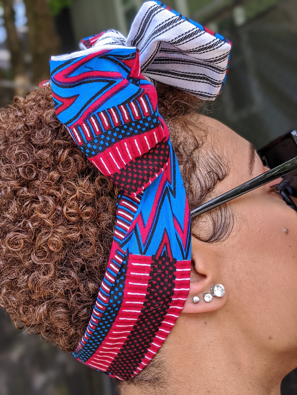 Short-haired woman wearing Kente and stripe print bow in head