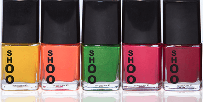 Five bottles of nail polish in yellow, coral, green, fuschia and burgundy are lined up in a brightly lit manner