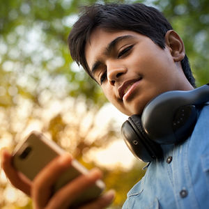 Jeune adolescent écoutant de la musique avec son téléphone intelligent.