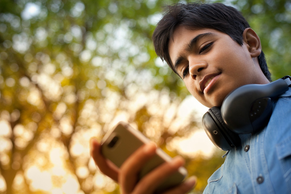 Indian student browsing his mobile phone