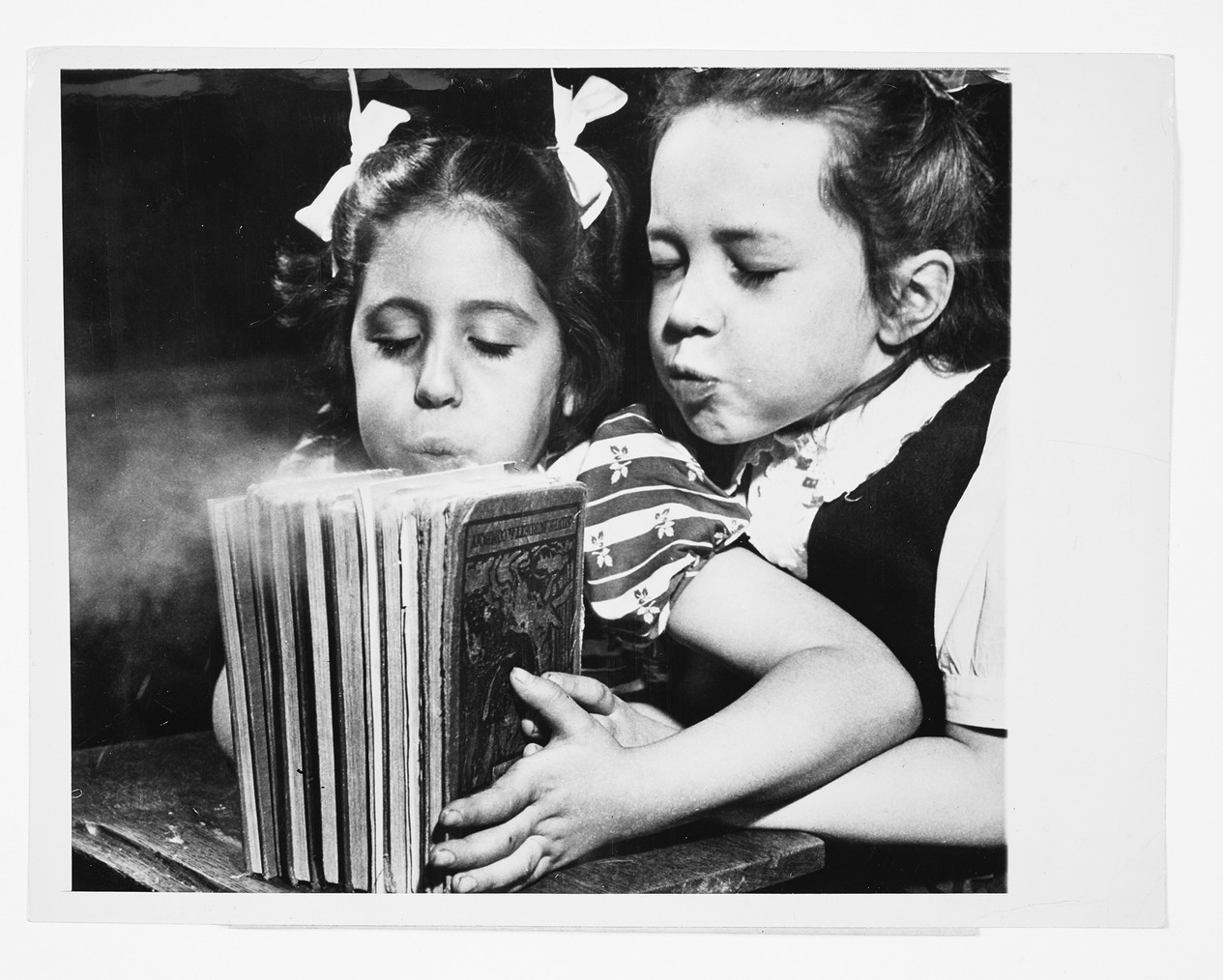 Photographer unknown, ACME Agency, School children blow 26 days of dust from their books as striking teachers return to work, 23 March 1948.