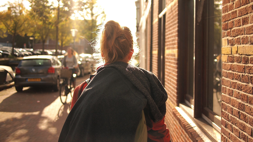 Woman walking down a sunlit street. Relationship problems