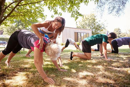 female-instructor-leading-outdoor-yoga-c