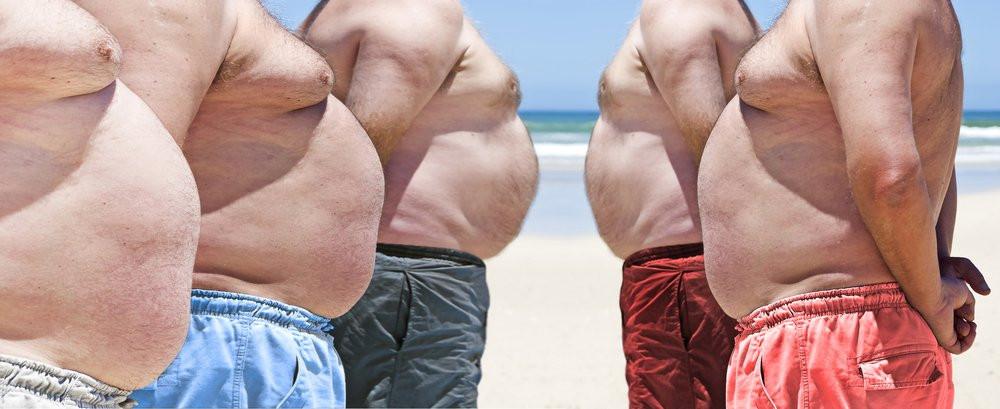 Vijf mannen op het strand, met een een uitpuilende broodbuik boven hun zwemshort, bespreken het boek van William Davis