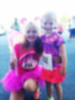 Woman runner with fairy wings and a wand, posing with a young girl