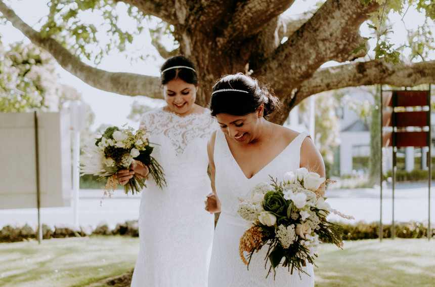 Two brides with bouquets under a tree