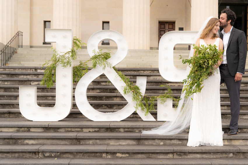 Bride and groom next to letters of their initials