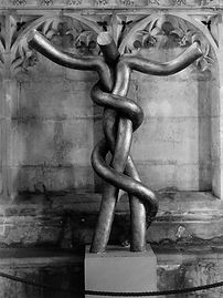 "Please note - this exhibition began before the COVID-19 lockdown, so will remain on display for the time being. An end date has not yet been set.  ""Lord of the Dance"" is the title of a sculpture Simon Latham made in 1990 when he was resident artist at Peterborough Cathedral. It is composed of three entwined, tubular elements, and creates a lively, cruciform figure.   The title is shared with Sydney Carter's well-loved hymn and the Hindu god Shiva. The image can be seen as a reference to the crucified Christ (""He opened wide his arms for us on the cross"") and draws to mind the Brazen Serpent, made by Moses and raised on a staff as a symbol of healing to the Israelites in the wilderness, which Christ understood to prefigure his own crucifixion. It also invites comparison with the snake entwined staff of Asclepius, who of all the gods of the ancient world is nearest to the ideal of Christ: his walking stick and snake is now a universal symbol of the medical profession.   Last year, Simon decided to recreate the life-sized sculpture that once stood in Peterborough Cathedral, the other pieces were made between 1989 and 1992. He is delighted that these exhibits can be seen again together as a group. Some are carved from wood and others are made of plaster. Variations on the theme include a seated Christ in Majesty, often represented in cathedral carvings, and a reclining figure originally referring to St Paul at his conversion. Drawings, paintings and prints exploring the theme are exhibited with the sculptures alongside original photographs. It is imagery of hope, faith and sacrificial love,and he hopes you find it visually pleasing, still of interest and worth visiting.   The graphic work includes four charcoal drawings: one each of his first two woodcarvings, another showing three views of the small plaster torso figure, the last showing the reclining St Paul torso figure. There are three small black and white paintings exploring the confrontation of the two torso figures, and a colour poster of Sebastien Bourdon's ""Brazen Serpent"" (1660) Prado Museum, Madrid.    Simon Latham was born in 1964. He graduated from Oxford University as a Bachelor of Fine Art in 1987. Before coming to Peterborough Cathedral, he was Resident Artist at Plymouth College and Repton School. He became an Art Teacher in 1994 and has taught at schools in London and Dorset. In 2017, he retired from teaching and has been picking up the threads of past ideas and developing new ones.   FREE ENTRY TO EXHIBITION ONLY"