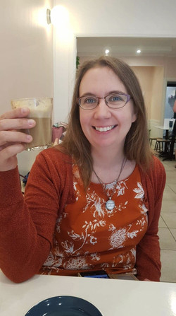 Jo is a blond woman, 40 years old, she is wearing a orange top and glasses. She is toasting the came
