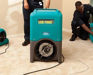 Cleaners use industrial fans to dry out a flooded home.