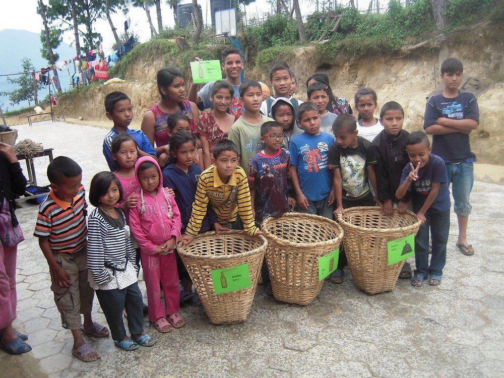Children with new trash baskets to use in their home