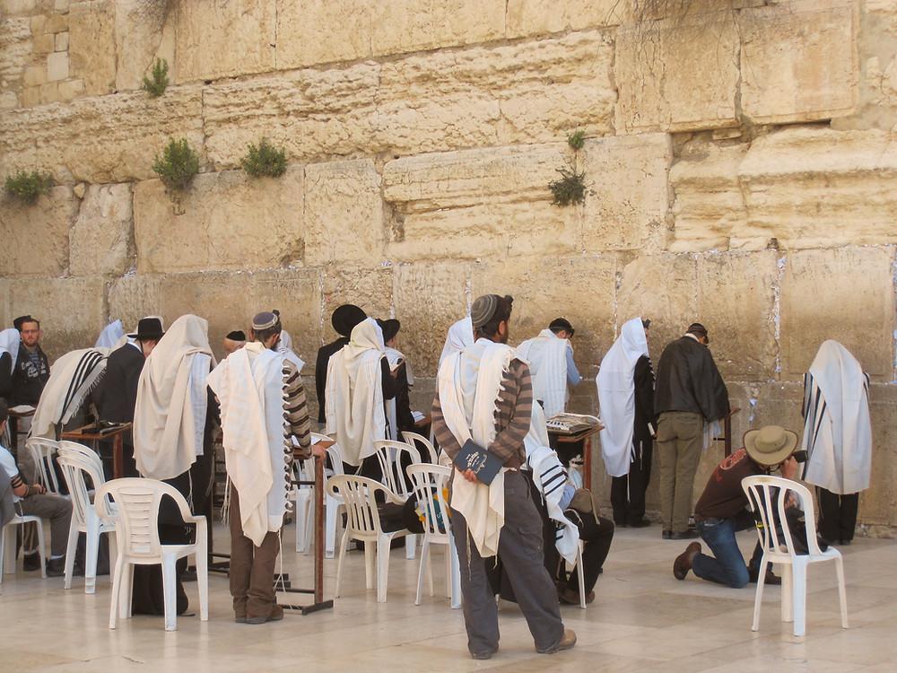 Men praying at the Western Wall on Tisha B'Av