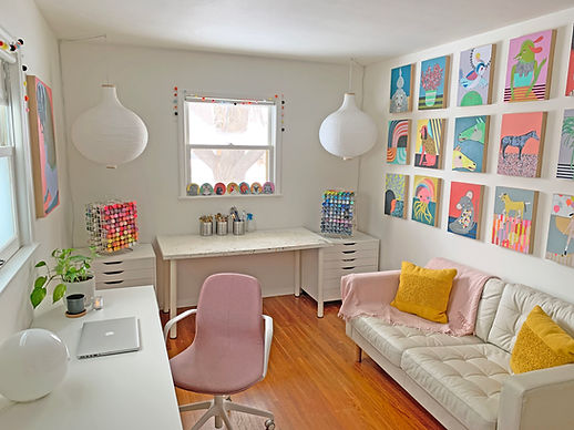 The home studio of Minneapolis Artist Jennifer Davis featuring her desk, worktable, a sofa and a wall of colorful paintings.