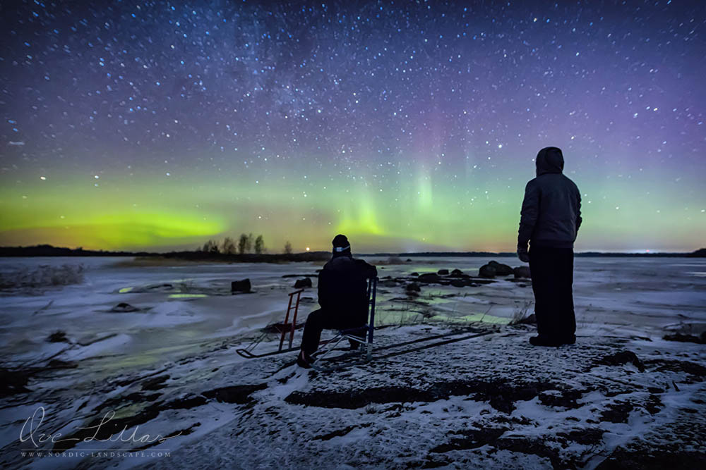 Two men with kicksleds standing on a rock and watching the Aurora Borealis reflecting in the ice