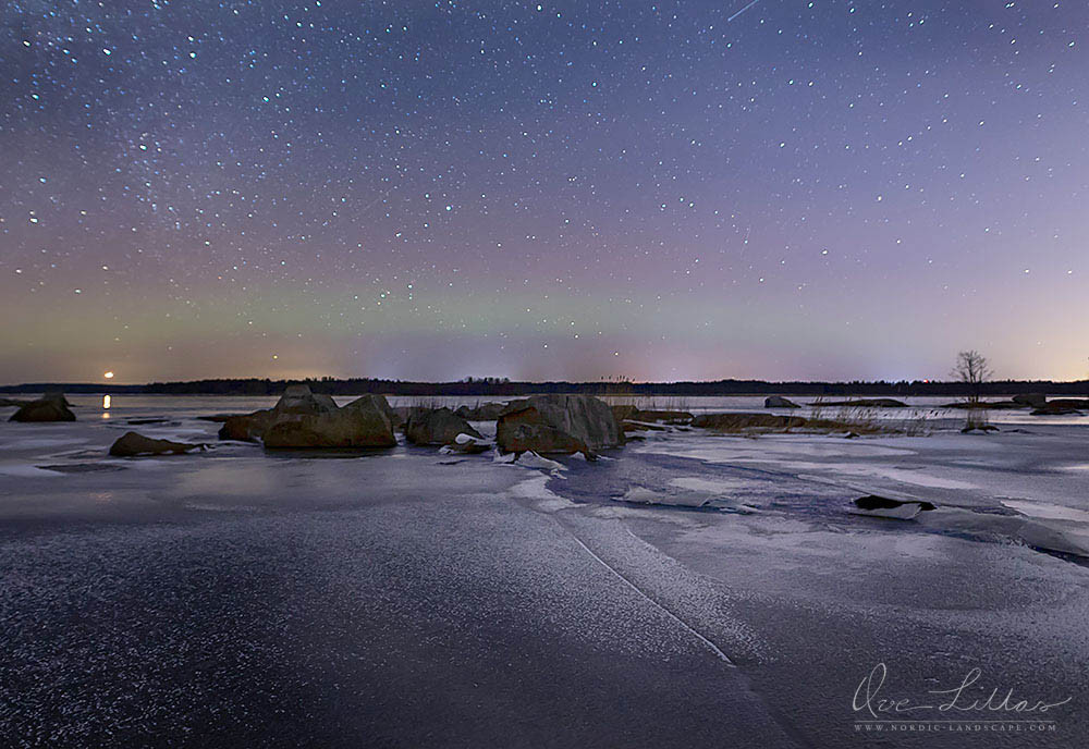 Northern Lights starting to appear over the ice and some rocks