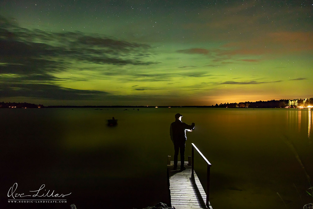 Ove standing on a bridge holding an electrical lantern. Aurora Borealis on the night sky.