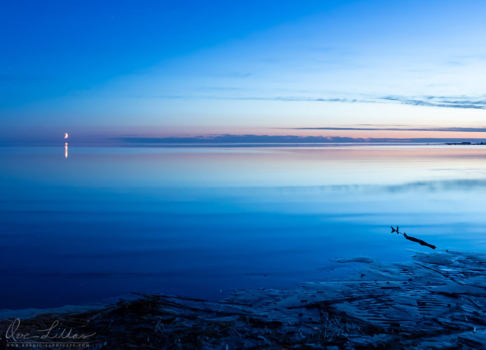 Morning light and the moon reflected in a calm sea.