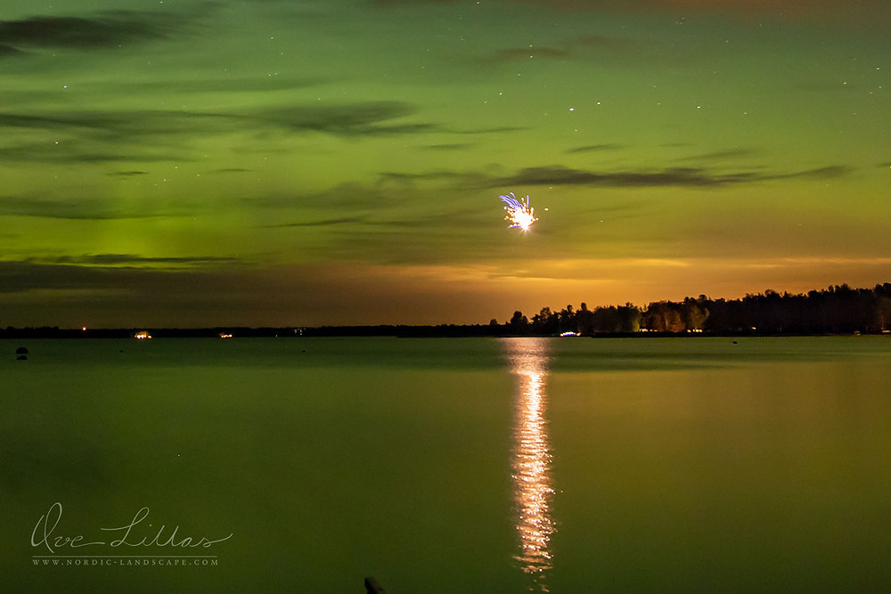 Fireworks reflecting in the sea. The Northern Lights decorating the sky.