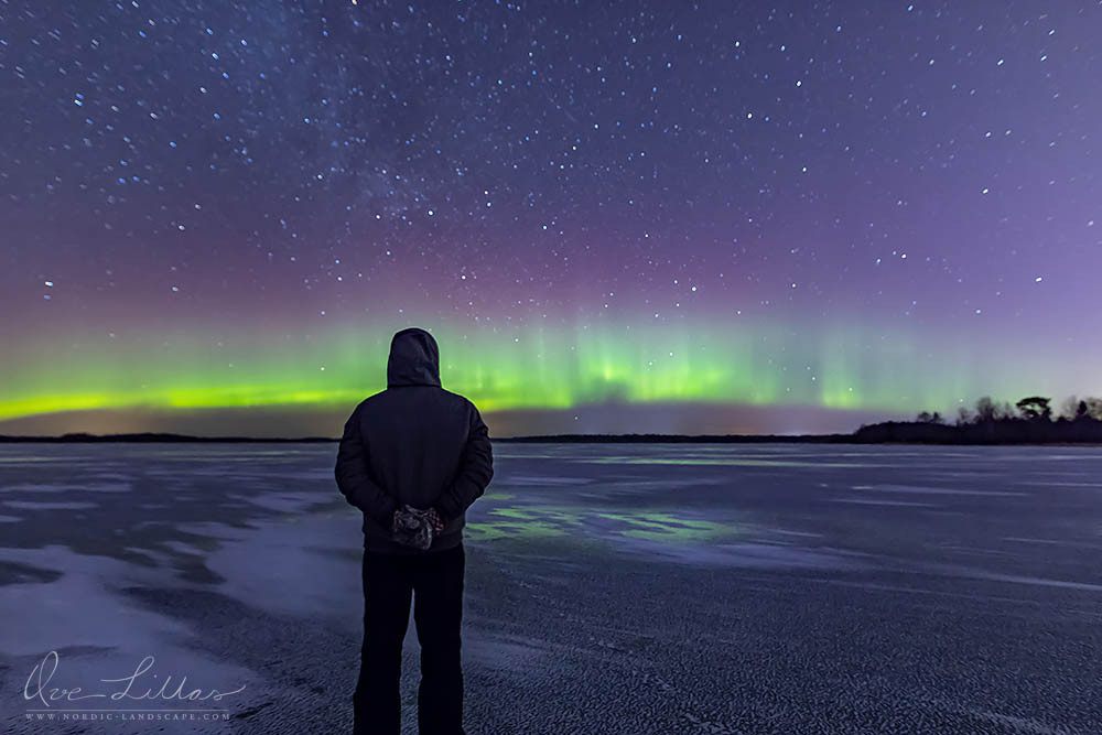 Man standing on the ice and watching the Northern Lights