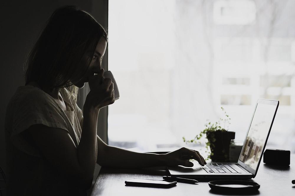 mulher usando laptop enquanto toma xícara de café