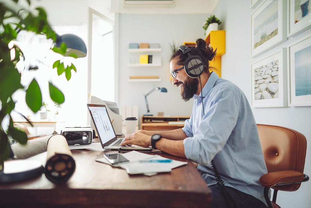 homem sentado trabalhando no computador com fone de ouvido