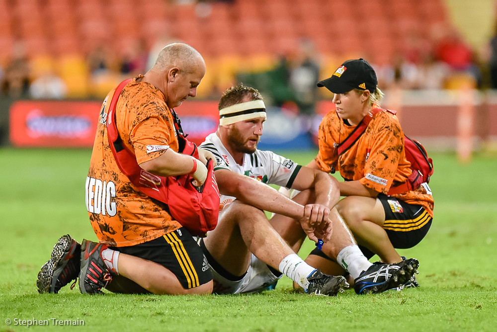 Sam Prattley is checked by medical staff after clashing heads with Jono Lance