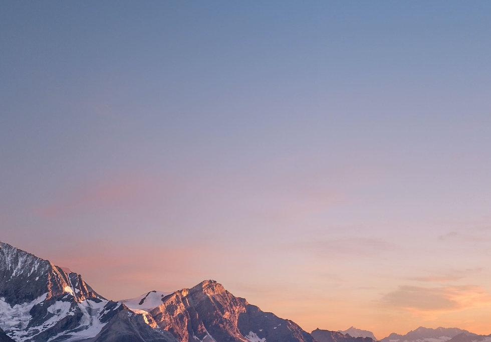 Snowy mountain cap during a orange sunset