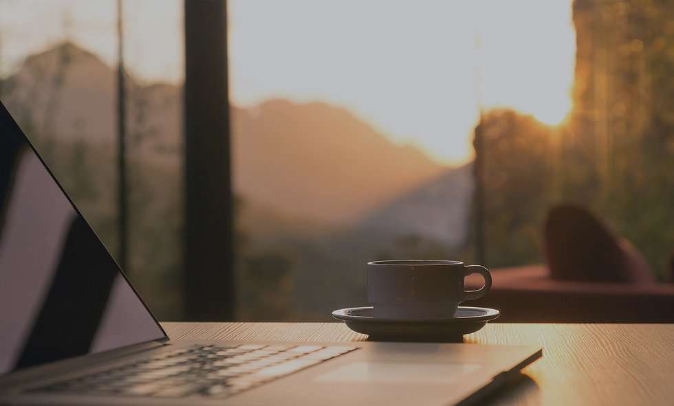 A cup and laptop ontop of a desk with the sunset in the background