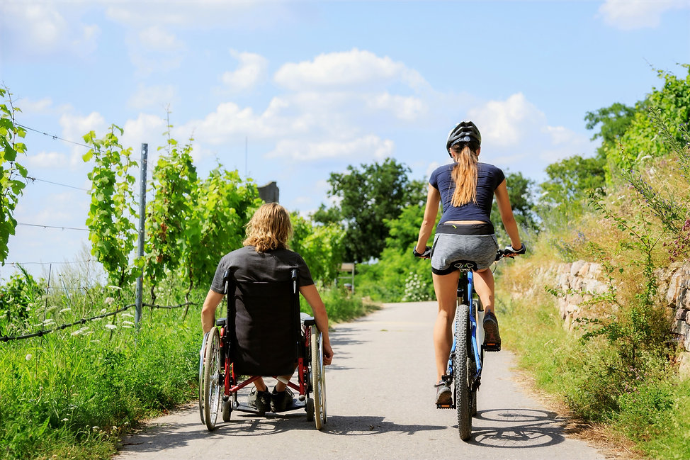 Image Description: Man and woman riding down a bike path together. One using a wheelchair and one on a bike.