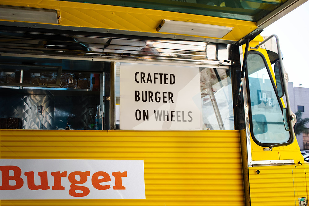 bright yellow food truck serving hamburgers