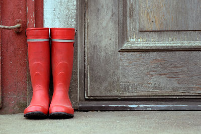 Red wellies outside of old house. Horizo