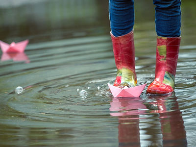 girl runs the pink paper boat in a puddl