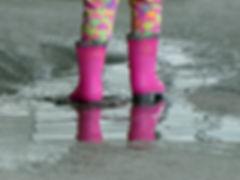 Little girl wearing pink rain boots stan