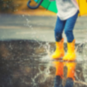 Feet of child in yellow rubber boots jum