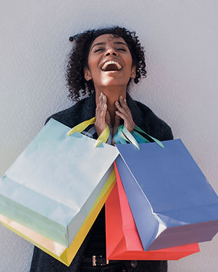 happy-young-black-woman-with-shopping-ba
