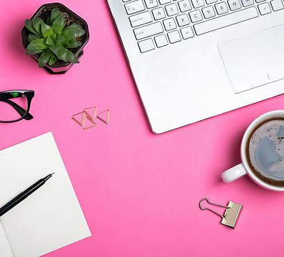 Pink desktop with laptop coffee mug pen paper succulent and glasees
