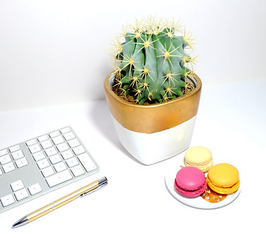 White desktop with white keyboard, small white plate of colorful macaroons, gold and white pot holding a cactus, gold pen